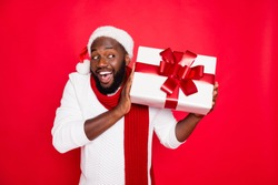 Portrait of amazed funky dark skin man wear santa claus headwear hold big package receive on x-mas  time celebration scream wow feel interested wear style pullover isolated over red color background