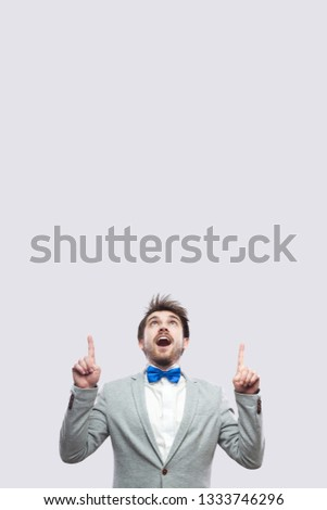Portrait of amazed handsome bearded man in casual grey suit and blue bow tie standing looking and pointing at up copyspace. studio shot, isolated on light grey background.