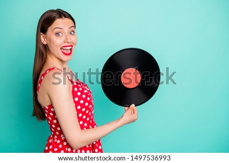 Portrait of amazed lady holding vinyl record screaming wow omg wearing dotted skirt dress isolated over teal turquoise background