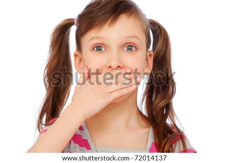 portrait of amazed small girl covering her mouth over white background