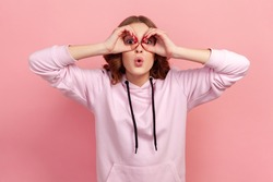 Portrait of amazed teen girl with curly hair in hoodie looking through binoculars gesture and expressing surprise, zooming vision, exploring distance. Indoor studio shot isolated on pink background