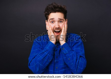 Portrait of amazed young trendy man standing over dark background