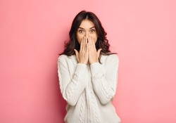 Portrait of amazed young woman over pink background