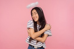 Portrait of amazing angelic girl with long brunette hair and halo over head smiling contentedly and hugging herself, concept of self-love, support. indoor studio shot isolated on pink background