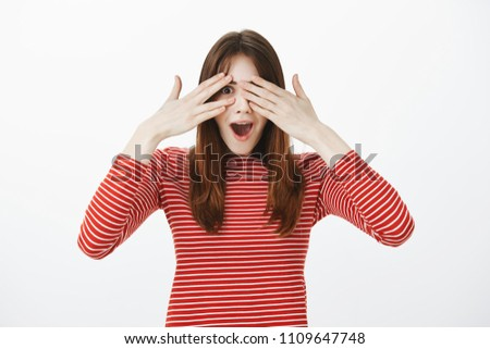 Portrait of amazing european girl in casual clothes, covering eyes and peeking through fingers being surprised and happy seeing great gift, standing over gray background upbeat