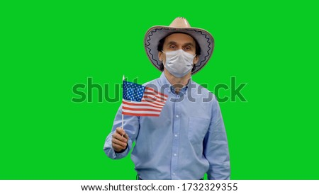 Photo of  Portrait of american man in protective mask and cowboy hat holds the USA flag on green screen background, Covid-19 Pandemic, Chroma key