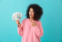 Portrait of american successful woman 20s with afro hairstyle holding lots of money dollar banknotes isolated over blue background