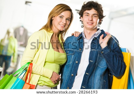 Portrait of amorous couple looking at camera with smiles after great shopping