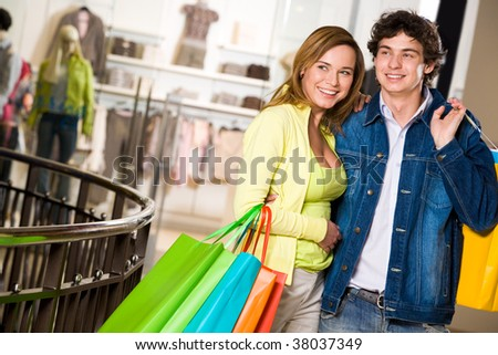 Portrait of amorous couple looking at something with smiles during shopping