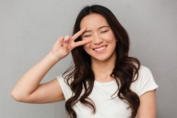 Portrait of amusing chinese girl 20s in casual t-shirt having fun and holding two fingers at her face isolated over gray background