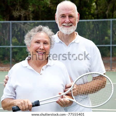 Portrait of an active senior couple on the tennis courts.