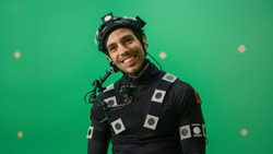 Portrait of an Actor Wearing Motion Caption Suit and Head Rig Posing with Green Screen Background. Film Studio Set Shooting Blockbuster Movie with Chroma Key.