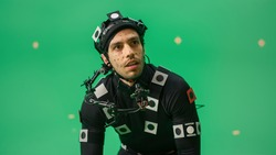 Portrait of an Actor Wearing Motion Caption Suit and Head Rig Posing with Green Screen Background. Big Budget Filmmaking On Film Studio Set Shooting Blockbuster Movie with Chroma Key.