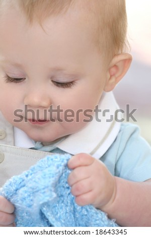 Portrait of an adorable baby boy holding a blue blanket