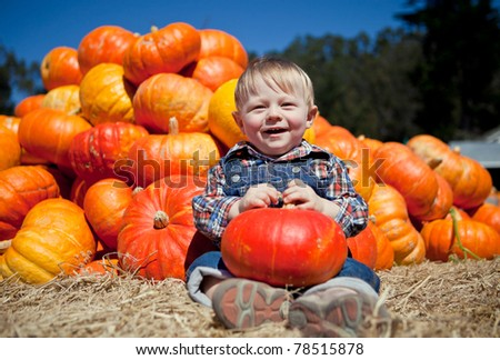 Portrait of an adorable baby boy with a pumpkin