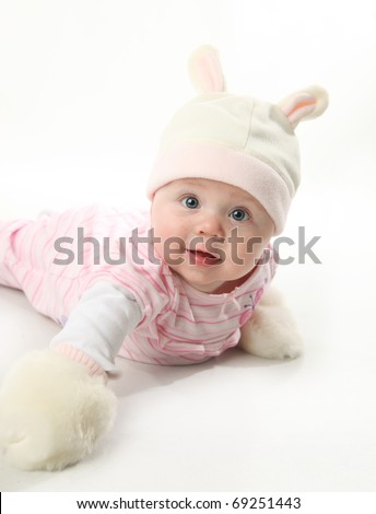 Portrait of an adorable baby girl wearing a bunny rabbit costume and furry mittens