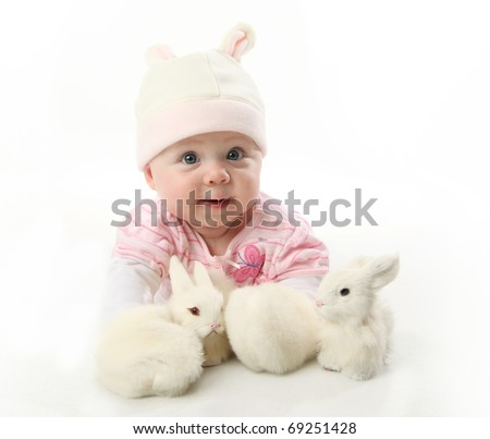 Portrait of an adorable baby girl wearing a bunny rabbit costume and petting two white bunnies