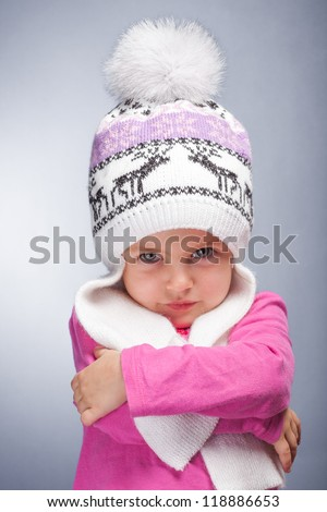 Portrait of an adorable baby girl wearing a knit pink and white winter hat.