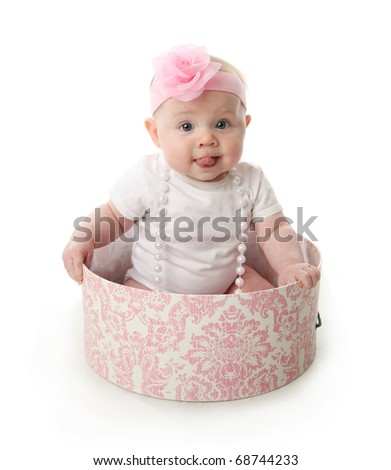Portrait of an adorable baby girl with tongue sticking out sitting in a pink and white hatbox wearing a white shirt, pearl necklace, and pink headband with rose