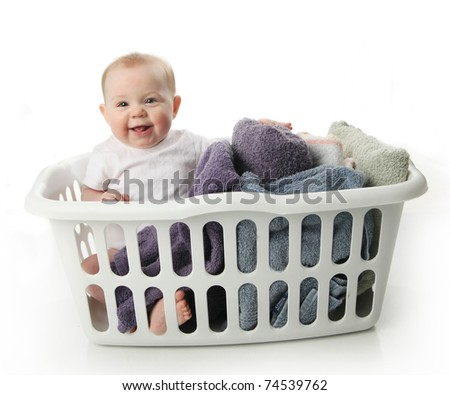 Portrait of an adorable baby sitting in a laundry basket with towels