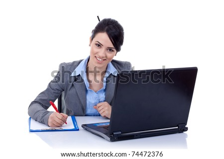 Portrait of an adorable business woman working at her desk with a laptop and paperwork.