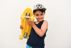 portrait of an adorable child holding a yellow skateboard in his hands, isolated on a white background