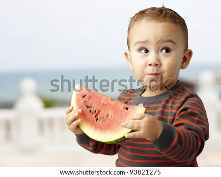 portrait of an adorable kid tasting a watermelon slice against a shore background
