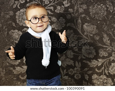 portrait of an adorable kid wearing glasses gesturing doubt against a vintage background - stock photo