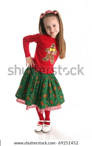 Portrait of an adorable preschool age girl wearing a Christmas holiday outfit with a gingerbread man and candy canes