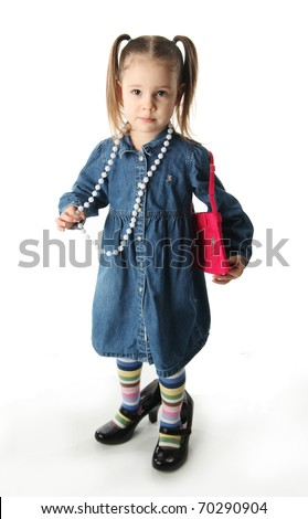 Portrait of an adorable preschool girl playing dress up with a mother's shoes, purse, and pearl necklace isolated on white