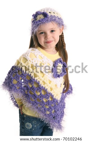Portrait of an adorable toddler girl wearing handmade crochet clothes, a shawl and hat in purple and yellow