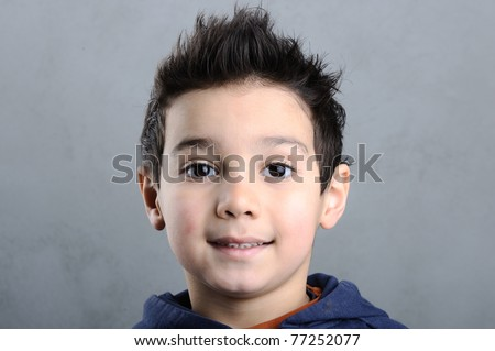 Portrait of an adorable young preschool boy with funny hair on dark background