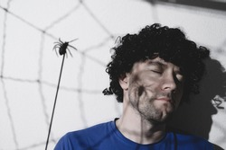 Portrait of an adult man in a black wig with a shadow of a spider and cobwebs on his face. Creates creepy puppet shadows. Halloween. Copy space