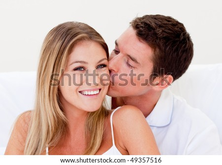Portrait of an affectionate man kissing his wife sitting on bed at home