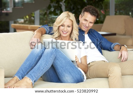 Portrait of an affectionate middle aged couple sitting with a laptop at home. Beautiful blond woman using laptop while handsome man sitting next to her and enjoy surfing on internet.