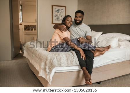 Portrait of an affectionate young African American couple laughing while sitting in their pajamas on their bed in the morning