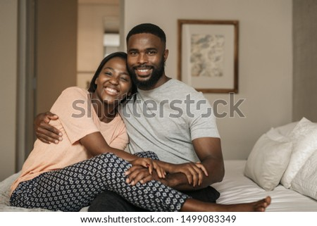 Portrait of an affectionate young African American couple smiling while sitting in their pajamas on their bed in the morning