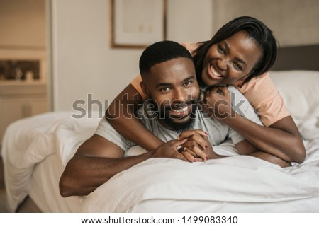 Portrait of an affectionate young African American woman lying on top of her smiling husband's back on their bed in the morning