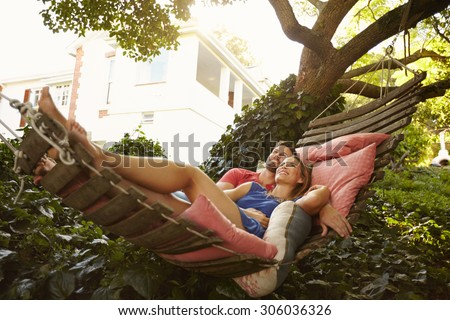 Portrait of an affectionate young couple lying on a hammock looking away smiling. Romantic young man and woman on garden hammock in backyard.