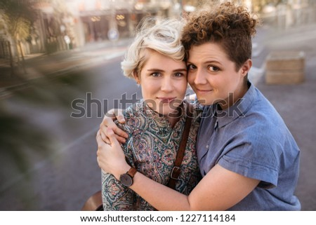Portrait of an affectionate young lesbian couple hugging each other while standing together on a city street #1227114184