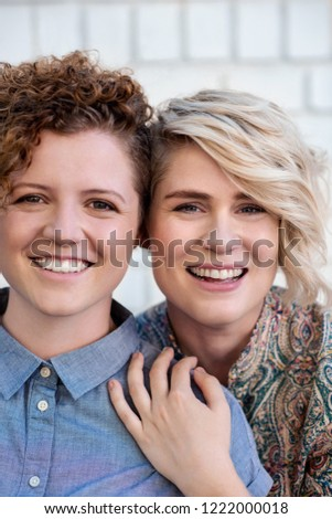 Portrait of an affectionate young lesbian couple smiling while standing together in front of a brick wall outside #1222000018
