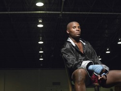 Portrait of an African American boxer sitting on chair