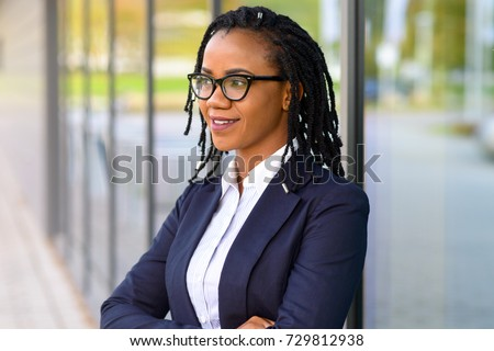 Portrait of an African American business woman with rastafarian dreadlocks and eyeglasses looking away with confidence while thinking outdoors