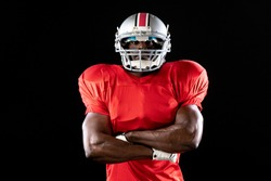 Portrait of an African American male American football player wearing a team uniform, pads and a helmet standing with arms crossed