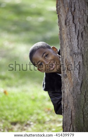 Portrait of an African American male child outdoors in Autumn being playful
