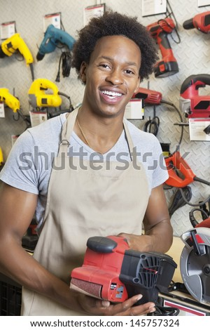 Portrait of an African American male store clerk holding electronic tool