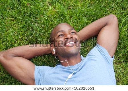 portrait of an African American man lying in grass listening to music