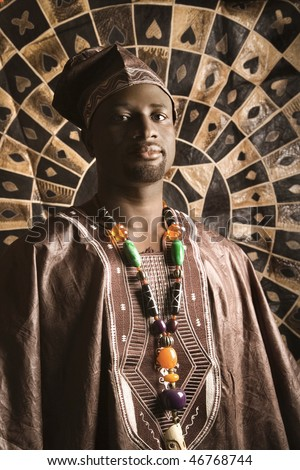 Portrait of an African American man wearing traditional African clothing, in front of a patterned wall and looking at the camera. Vertical format.