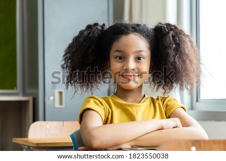 Portrait of an African American student girl in the classroom. She smiled happily. Back to school concept Stock photo ©