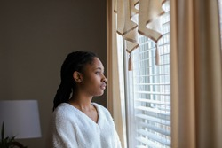 Portrait of an African-American teenaged girl looking out a window and feeling sad and lonely-teen